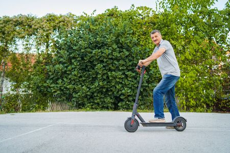 Senior man riding driving kick push scooter on the asphalt in front of the bushes green fence in a summer day Reklamní fotografie