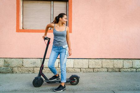 Young woman standing by the electric kick scooter board on the pavement in front of the wall of some house in the town looking back
