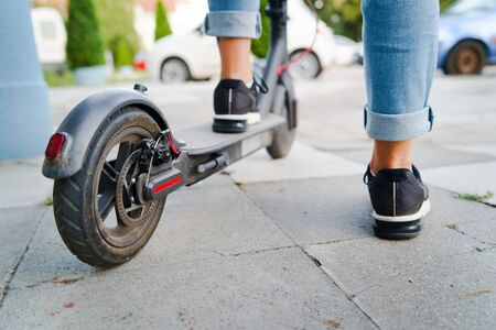 Close up on woman legs feet standing on the electric kick scooter on the pavement wearing jeans and sneakers in summer day back view
