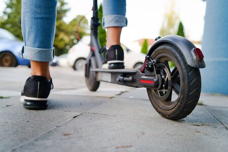 Close up on woman legs feet standing on the electric kick scooter on the pavement wearing jeans and sneakers in summer day back view riding