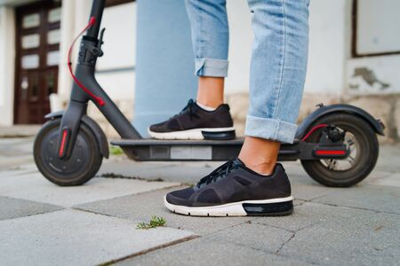 Close up on woman legs feet standing on the electric kick scooter on the pavement wearing jeans and sneakers in summer day side view riding