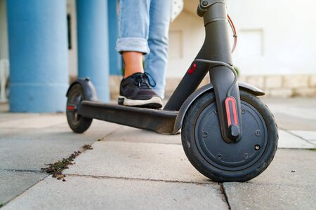 Close up on woman legs feet standing on the electric kick scooter on the pavement wearing jeans and sneakers in summer day