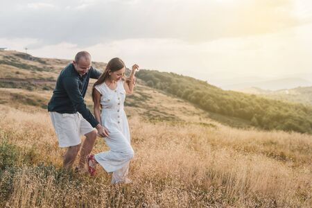 Young couple man and woman in love walking on the field on the mountain in autumn or summer day hugging together having fun bonding flirting flirt husband and wife lovers