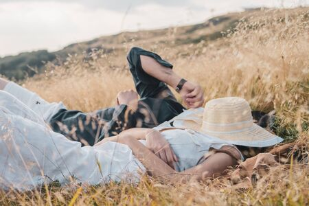 Young couple man and woman in love on the field on the mountain in autumn or summer day laying lay on the ground together having fun bonding holding hands husband and wife lovers Фото со стока