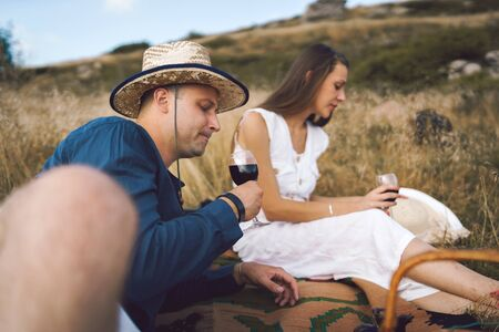 Young couple having a picnic on the blanket in the nature field on the mountain having a glasses of red wine celebrating love toasting on a date lovers happy in summer or autumn Фото со стока