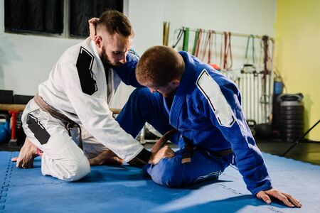 Brazilian Jiu Jitsu BJJ martial arts training sparring at the academy two fighters in butterfly guard position drilling techniques practicing in a gi kimono Stock Photo