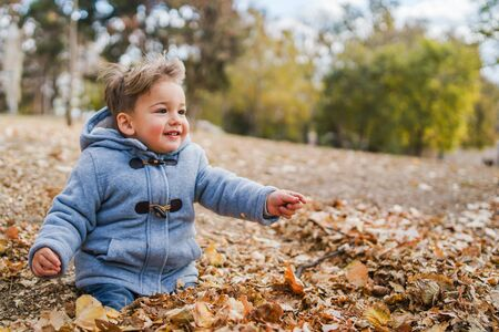 Portrait of small boy wearing coat playing with brown fallen leaves in park on the field in autumn day having fun in nature