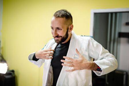 Young brazilian jiu jitsu BJJ or judo or karate fighter taking on his white gi kimono getting ready for the training martial arts class 版權商用圖片
