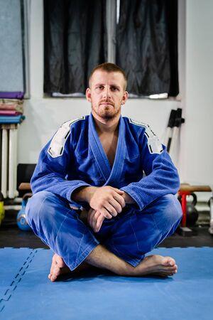 Young bjj brazilian jiu jitsu or judo athlete jujitsu fighter sittin on the tatami mats floor on the training wearing blue kimono gi