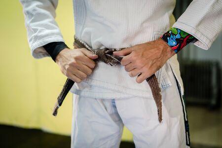 Close up on midsection of a man in martial arts gi kimono uniform tying his brown BJJ brazilian jiu jitsu belt around his waist in training at the academy