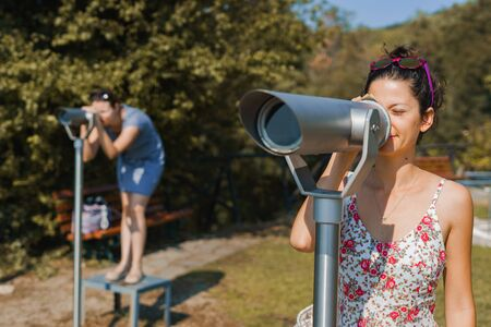 Young woman tourist in summer dress using monocular telescope binoculars to watch the scene from the mountain at the Aristotle's park at Stagira Greece in autumn