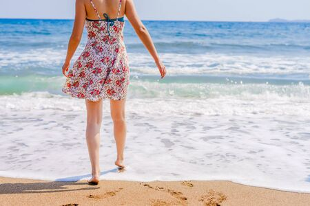 Woman walking on the beach to the sea in summer dress barefoot legs feet with footprints on the vacation holiday beach travel seashore ocean