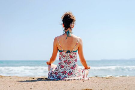 Young woman in summer dress practice yoga meditating at the beach by the sea or ocean in sunny day stretching meditation relaxing meditate lotus position back view Reklamní fotografie