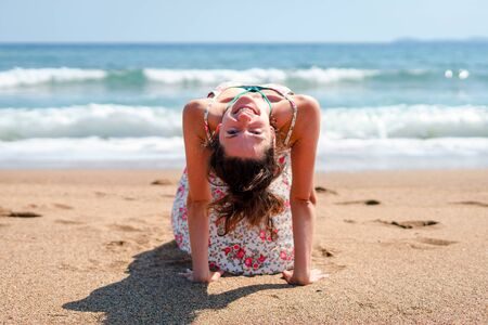 Young woman in summer dress practice yoga at the beach by the sea or ocean in sunny day stretching Reklamní fotografie