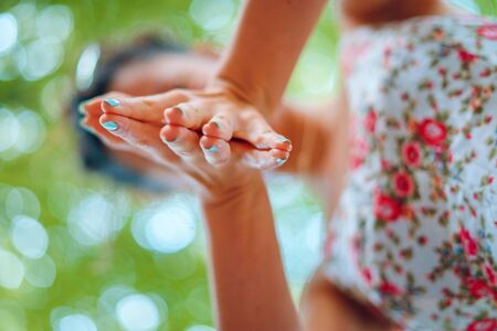 Young woman holding her hands together with fingers stretched apart close up selective focus Stock Photo