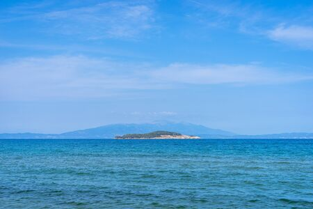 Seaside view horizon of the ocean water with an kafkanas island on the horizon in sunny day from the beach at Olympiada Greece Reklamní fotografie