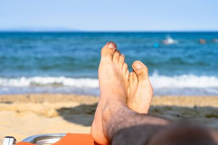 Feet foot of a man male at the beach by the sea in sunny day relaxing on vacation seaside by the ocean