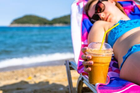 Close up on female girl woman hand holding a frappe or ice coffee at the beach while relaxing in a sunbed at vacation in sunny day
