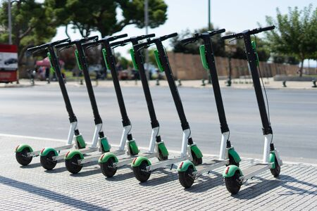 Lime Electric push kick scooter sharing rentals in sunny day by in a row scooters by the street on the sidewalk in a city thessaloniki ready to ride or rent 版權商用圖片 - 131748637