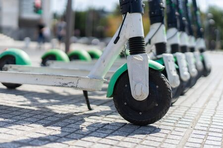 Lime Electric push kick scooter sharing rentals in sunny day by in a row scooters by the street on the sidewalk in a city thessaloniki ready to ride or rent close up on wheel