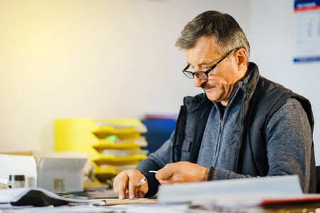 Senior man entrepreneur at his office store by the table accounting check bill calculation receipt making invoice for selling goods salesman at warehouse depot storehouse