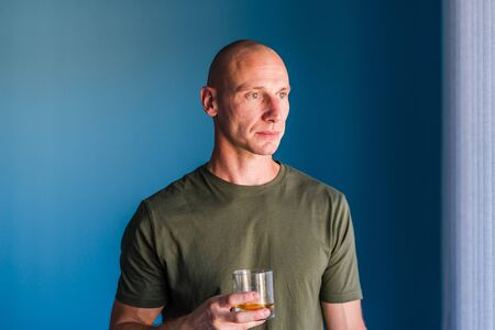 Portrait of young handsome man with short hair holding a glass of whiskey or brandy alcohol drink standing in front of blue wall looking trough the window Stok Fotoğraf