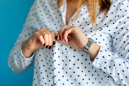 Close up on midsection of young women girl button or unbutton white shirt with spots in front of the blue wall at home alone changing clothes dressing or undressing hands