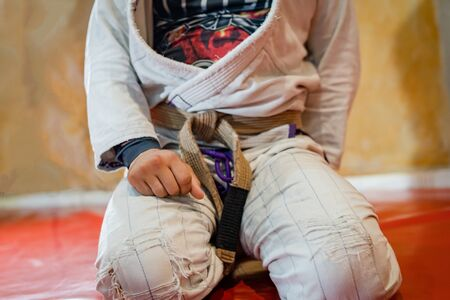 Close up on midsection of the bjj brazilian jiu jitsu athlete sitting on the mats tatami at the training class with hand on his tie wearing white gi kimono