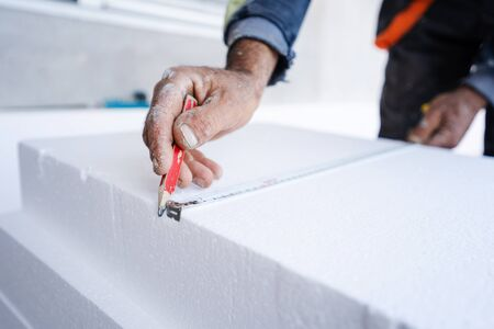 Worker use ruler measuring tape and pen to measure and mark the correct length of  during the wall insulation process at the construction site