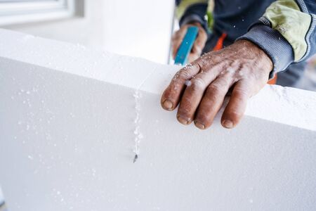 Construction worker using the hand saw to cut the  insulation panel table at the construction site in the insulating renovation procedure Reklamní fotografie