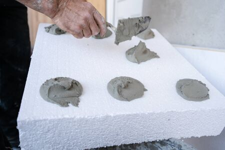 Worker hand with trowel applying cement adhesive glue on white on  wall insulation energy efficient concept at the construction site insulating renovation