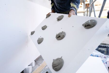 Worker placing  sheet insulation to the wall at construction site Rigid extruded polystyrene insulation board for energy saving Of Facade house renovation energy efficient