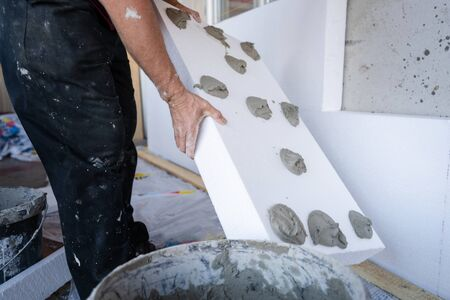 Worker hand holding panel with applied cement adhesive glue on white on  wall insulation energy efficient concept at the construction site insulating renovation Reklamní fotografie