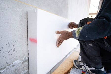 Worker placing sheet insulation to the wall at construction site Rigid extruded polystyrene insulation board for energy saving Of Facade house renovation energy efficient Reklamní fotografie