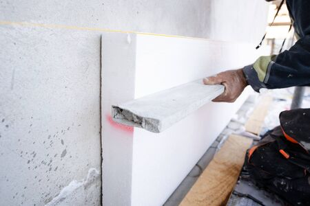 construction worker during the  house external wall insulation. Contractor with level checking the work in progress level of the boards
