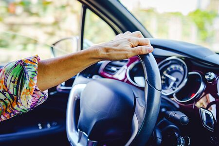 Woman driving a car wearing summer dress and sunglasses in a sunny autumn day close up on hand on the wheel