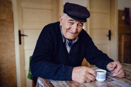Senior man grandfather old pensioner farmer wearing black sweater and hat having a cup of coffee or tea by the table at home sitting alone smiling
