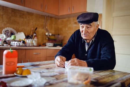Senior man grandfather old pensioner farmer wearing black sweater and hat having a cup of coffee or tea by the table at home sitting alone lonely sad