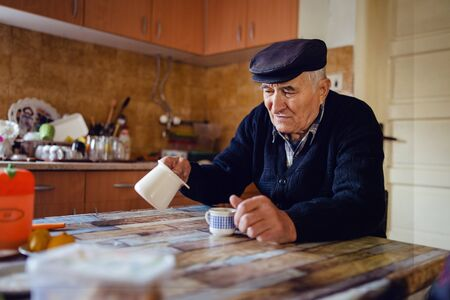 Senior man grandfather old pensioner farmer wearing black sweater and hat having a cup of coffee or tea by the table at home sitting alone pouring coffee from the pot