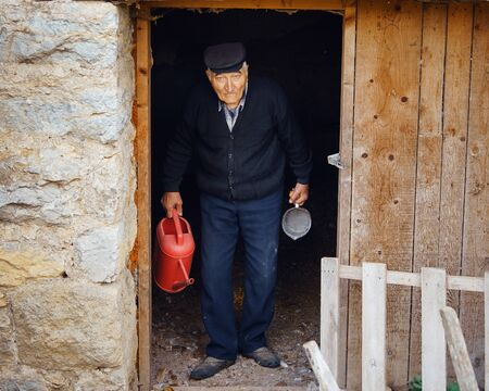 Senior man grandfather pensioner standing in the door of the farm object barn or piggery or hen house holding red water bucket