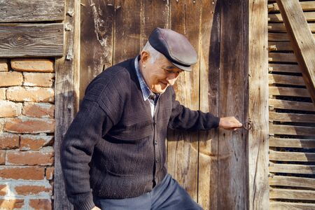 Senior man farmer old pensioner grandfather getting out from the old barn house at the farm in autumn day closing the wooden door Reklamní fotografie