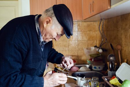 Senior man grandfather old pensioner farmer wearing black sweater and hat making a cup of coffee or tea cooking in the pot at home putting coffee to the pot with spoon