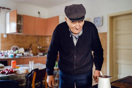Senior man grandfather old pensioner farmer wearing black sweater and hat having a cup of coffee or tea cooking in the pot at home waiting to boil Reklamní fotografie