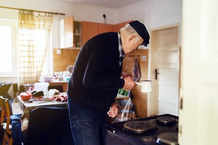 Senior man grandfather old pensioner farmer wearing black sweater and hat having a cup of coffee or tea cooking carry the pot at home