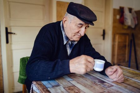 Senior man grandfather old pensioner farmer wearing black sweater and hat having a cup of coffee or tea by the table at home sitting alone Reklamní fotografie