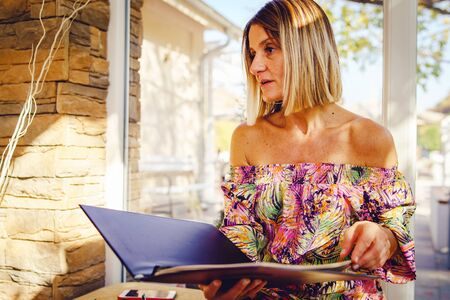 Portrait of caucasian woman sitting in cafe or restaurant holding menu looking to choose order wearing summer dress