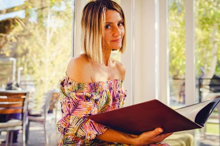 Portrait of caucasian woman sitting in cafe or restaurant holding menu looking to the camera wearing summer dress