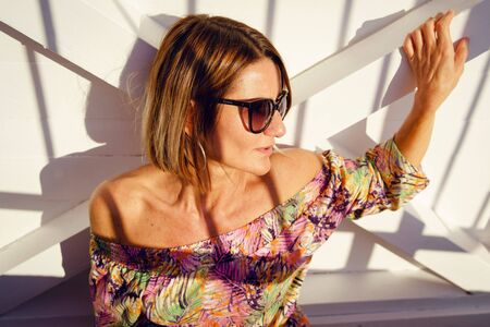 Portrait of beautiful mature woman in sunny summer or autumn day wearing dress and sunglasses standing posing in front of white door waiting for somebody with shades on her face