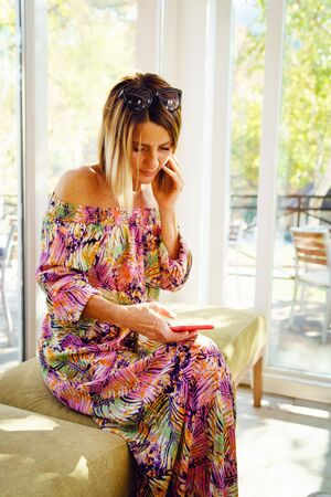 Portrait of mature woman using her mobile smart phone at the cafe or restaurant wearing summer dress in sunny day sitting by the window looking to display call or message Reklamní fotografie