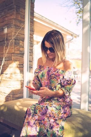 Portrait of mature woman using her mobile smart phone at the cafe or restaurant wearing summer dress in sunny day sitting by the window looking to display photo or message